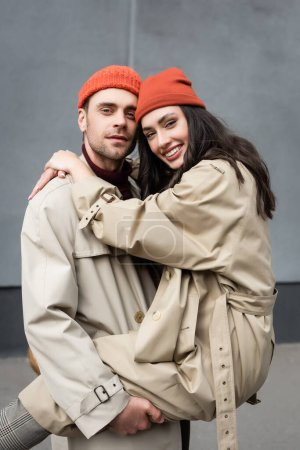 Photo pour Stylish man holding in arms woman in beanie hat and trench coat - image libre de droit