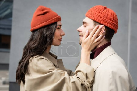 Photo for Side view of trendy woman touching man in beanie hat - Royalty Free Image