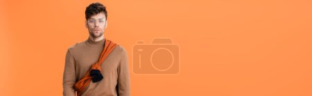 Photo pour Horizontal image of trendy man in autumn outfit and glasses isolated on orange - image libre de droit