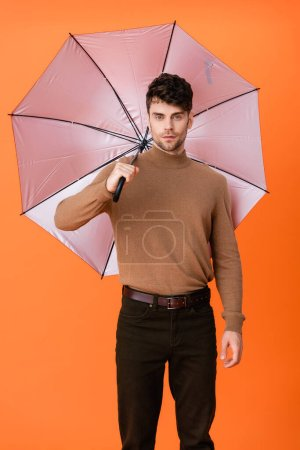 Photo pour Élégant homme en tenue d'automne debout sous le parapluie sur orange - image libre de droit