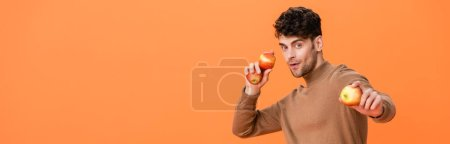 Photo pour Panoramic crop of man in autumn outfit holding fresh apples isolated on orange - image libre de droit