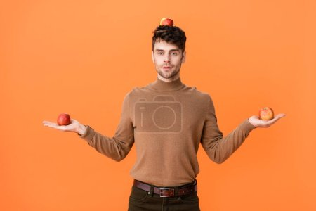 Photo for Man in autumn outfit holding fresh apples on head and hands isolated on orange - Royalty Free Image