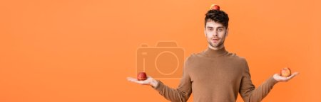 Photo pour Panoramic crop of man in autumn outfit holding fresh apples on head and hands isolated on orange - image libre de droit