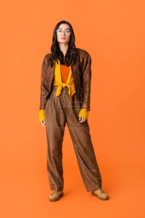 Photo for Full length of stylish woman in autumn outfit and glasses standing on orange - Royalty Free Image