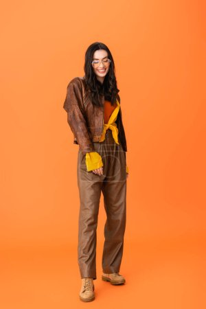 Photo pour Full length of young woman in autumn outfit and glasses standing on orange - image libre de droit
