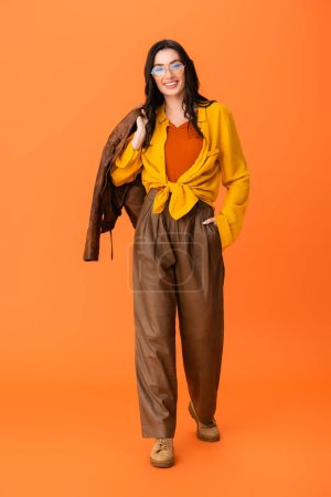 Photo pour Full length of joyful woman in autumn outfit holding leather jacket and standing with hand in pocket on orange - image libre de droit