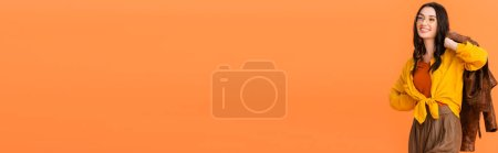 Photo for Horizontal crop of joyful woman in autumn outfit holding leather jacket and standing with hand on hip isolated on orange - Royalty Free Image