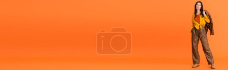 Photo pour Panoramic orientation of woman in autumn outfit holding leather jacket on orange - image libre de droit