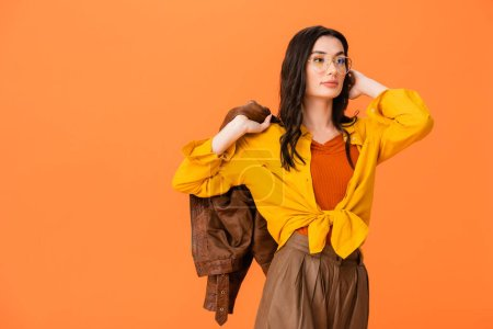 Photo for Trendy woman in glasses and autumn outfit holding leather jacket while standing isolated on orange - Royalty Free Image