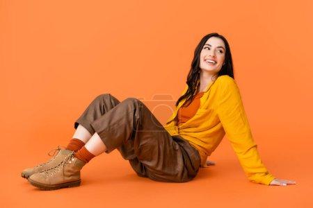 Photo pour Femme joyeuse en tenue d'automne et bottes regardant loin tout en étant assis sur orange - image libre de droit