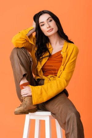 Photo pour Trendy woman in autumn outfit sitting on white stool and looking at camera isolated on orange - image libre de droit