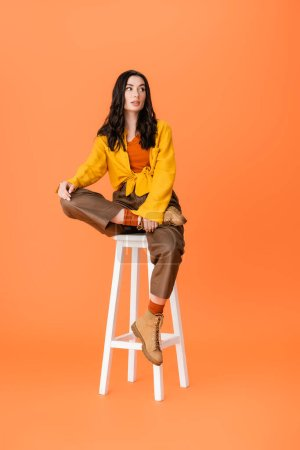 Photo pour Fashionable woman in autumn outfit sitting on white stool and looking away on orange - image libre de droit