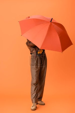 Photo for Full length of fashionable woman in autumn outfit and boots covering face with umbrella on orange - Royalty Free Image