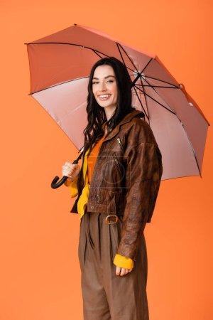 Photo pour Jeune femme en tenue d'automne debout sous parapluie isolé sur orange - image libre de droit