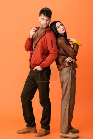 Photo for Full length of trendy couple in leather jackets posing on orange - Royalty Free Image