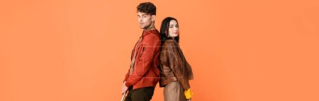 Photo pour Panoramic shot of fashionable man and woman standing back to back isolated on orange - image libre de droit