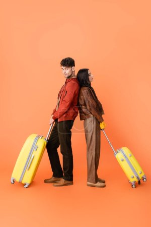 full length of stylish couple in autumn outfit standing back to back with yellow baggage on orange