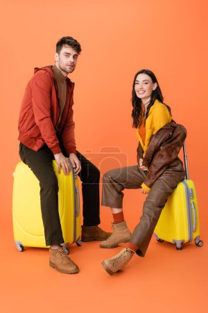 Photo pour Joyful and trendy couple in autumn outfit sitting on yellow baggage on orange - image libre de droit