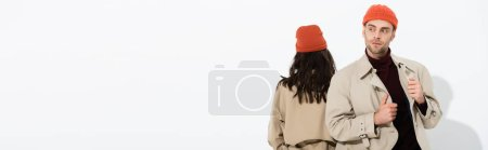 Photo pour Panoramic shot of stylish man in beanie hat touching trench coat near woman isolated on white - image libre de droit