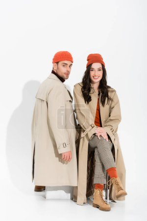 trendy couple in beanie hats and trench coats looking at camera on white