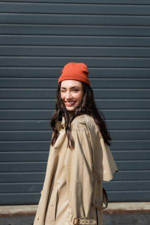Photo pour Joyful woman in trench coat and beanie hat winking eye - image libre de droit