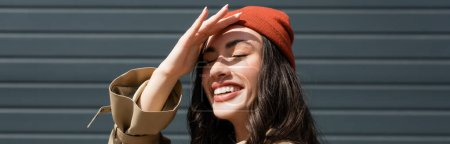 Photo pour Panoramic shot of stylish woman in beanie hat hiding from sunshine - image libre de droit
