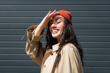 Photo pour Femme élégante et brune en bonnet chapeau se cachant du soleil avec la main - image libre de droit