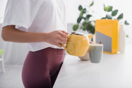 cropped view of young woman pouring tea from teapot in kitchen