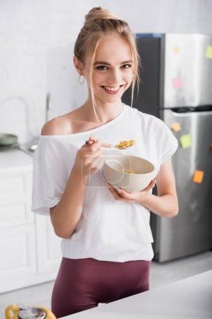 Photo pour Femme blonde en t-shirt blanc souriant à la caméra tout en mangeant des flocons de maïs pour le petit déjeuner - image libre de droit