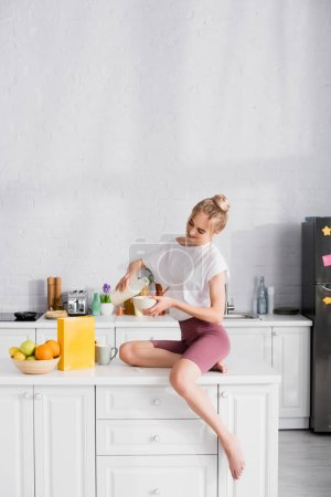 barefoot woman in shorts pouring milk into bowl while sitting on table in kitchen