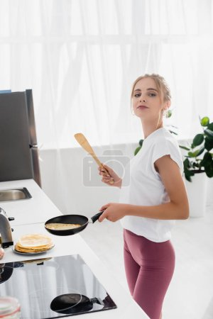 Photo for Young sensual woman holding spatula and frying pan while preparing pancakes for breakfast - Royalty Free Image