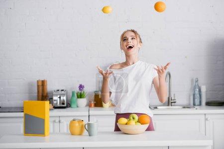 aufgeregte junge Frau jongliert mit frischen Früchten, während sie neben Teekanne und Tasse steht
