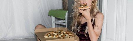 Photo pour Vue recadrée de jeune femme blonde mangeant de la pizza, image horizontale - image libre de droit