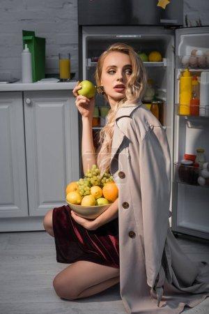 Photo pour Femme blonde en trench coat tenant bol avec des fruits frais près du réfrigérateur ouvert - image libre de droit