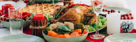 horizontal image of table served with delicious pie, roasted turkey and vegetables for thanksgiving dinner