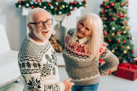 selective focus of cheerful man and woman looking at camera in room with christmas decoration