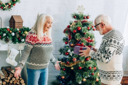 senior man holding gift box near excited wife standing with open arms near christmas tree