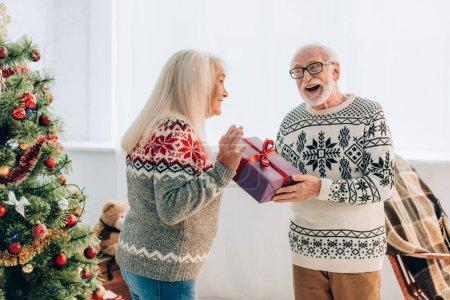excited senior man presenting gift box to happy husband near christmas tree