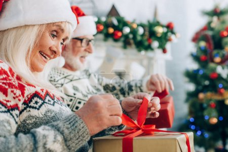 Photo pour Foyer sélectif de la femme âgée joyeuse ouvrir boîte cadeau près du mari - image libre de droit