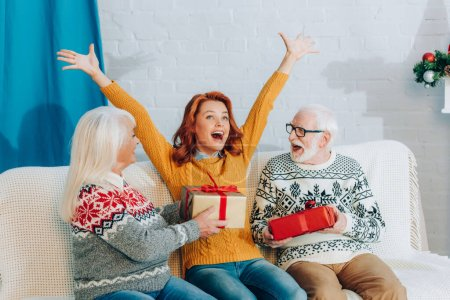 Photo pour Femme excitée avec les mains levées assis sur le canapé près des parents aînés tenant cadeaux de Noël - image libre de droit