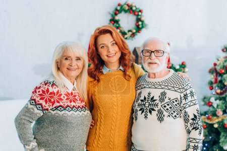 happy senior parents with daughter looking at camera in room with christmas decoration