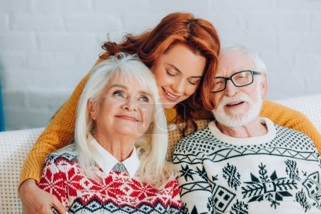 happy daughter embracing smiling senior parents with closed eyes