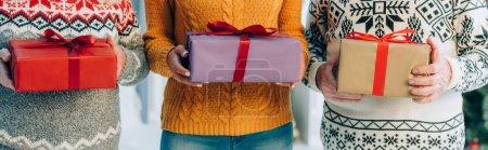 Photo pour Vue recadrée de la femme et des parents aînés tenant des boîtes avec des cadeaux de Noël - image libre de droit