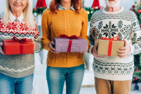 Photo for Cropped view of woman with senior parents holding christmas gift boxes - Royalty Free Image