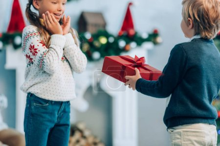 garçon présentant cadeau de Noël à la soeur étonnée tenant la main près du visage