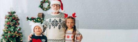 plan panoramique de grand-père embrassant ses petits-enfants dans des chapeaux de Père Noël
