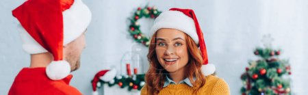 Photo for Panoramic shot of happy woman in santa hat looking at camera near husband - Royalty Free Image
