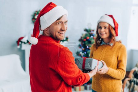 cheerful man looking at camera while presenting gift box to smiling wife