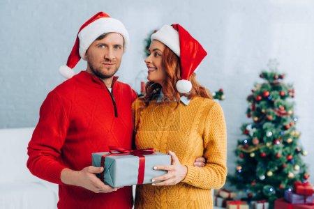 femme heureuse regardant la caméra tout en tenant boîte cadeau de Noël
