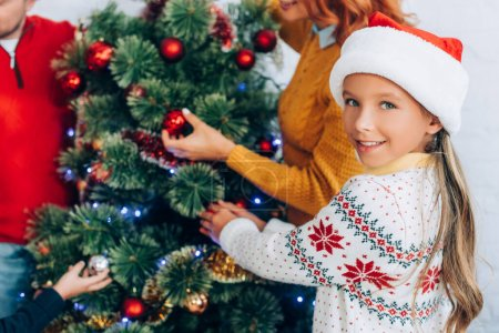 happy girl in santa hat looking at camera while decorating christmas tree together with family